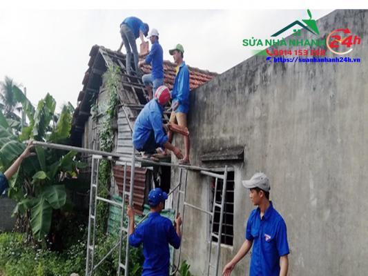 """Những người thợ áo xanh của """"đội thợ 0 đồng"""" xã Đức Ninh tất bật sửa xong ngôi nhà cho bà Đặng Thị Châu để kịp đón tết - Ảnh: QUỐC NAM"""